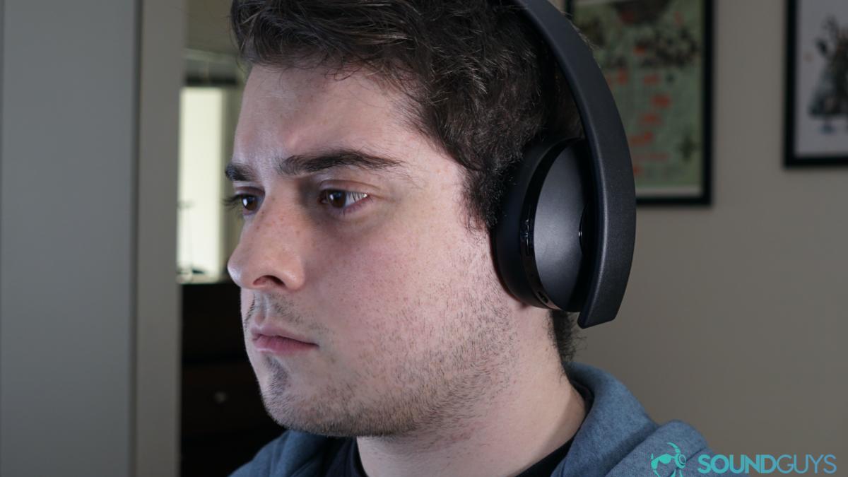 Bir adam bir Playstation altın kablosuz kulaklık takıyor oturuyor.