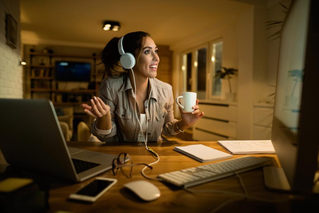 Kadınlar kulaklık ile video konferans masanın önünde tutun.