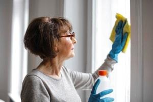 Žena stierajúca okno žltým kobercom